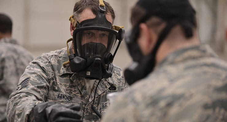 Staff Sgt. Jeffrey Fancher hands off a sample of a possible threat agent during training. Credit: Christopher Muncy
