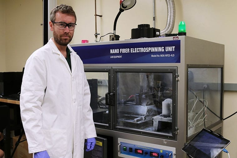 Army researcher in white lab coat in front of a Nano Fiber ElectroSpinning unit creating engineered carbon.