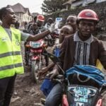 A man in a neon yellow safety vests checks temperatures wit a contactless laser thermometer. People in Goma wait in line for their turn
