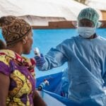 Masked health care provider takes temperature in Ebola treatment tent