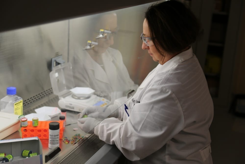 Researcher with intent look of focus, wearing safety glasses and lab coat, works with her gloved hands inside a large biosafety hooded laboratory bench area.