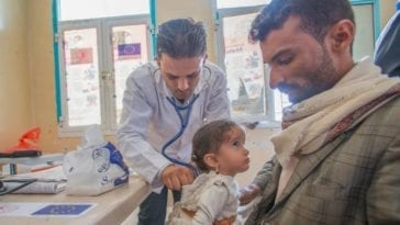 Doctor examines child for signs of influenza respiratory illness