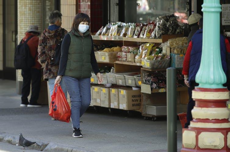 Woman walking in San Francisco's Chinatown wearing facemask