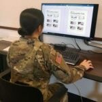 National Guardsmen sit in front of computer screen editing safety fliers from english to other languages