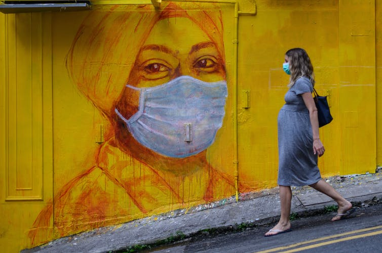 A pregnant woman walks past a street mural in Hong Kong on March 23, 2020